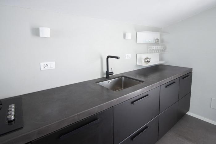 Mensole e scaffali in cucina con piano di lavoro in cemento